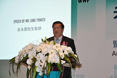 Long Yongtu presents a speech at the meeting