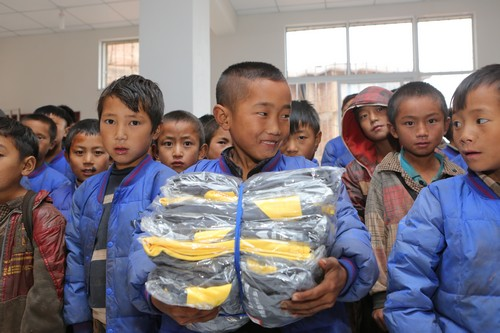 孩子们领到欧博娱乐救济的校服等物资,显露开心的愁容